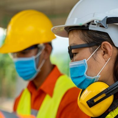 Engineer wearing protective mask to Protect Against Covid-19 working at construction site,Architect Engineer Meeting People Brainstorming Concept.
